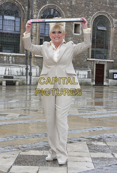 BARBARA WINDSOR.attends a photocall after receiving the Freedom of the City of London at the Guildhall, London, England, UK,.August 4th 2010.full length cream beige suit shirt jacket fringe holding over head raining trousers trouser .CAP/JIL.©Jill Mayhew/Capital Pictures