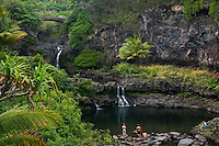 Young adults enjoying the seven pools and waterfalls at Ohe'o Gulch in HALEAKALA NATIONAL PARK on Maui in Hawaii USA