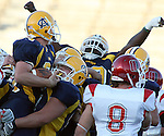Augustana College's Jordan Nordquist (34), left, is hugged and hoisted by teammate Clinton Berentschot (67) following a touchdown in the second quarter against the University of Nebraska Omaha Mavericks Saturday evening at Howard Wood Field in Sioux Falls. (photo by Dave Eggen/Inertia)