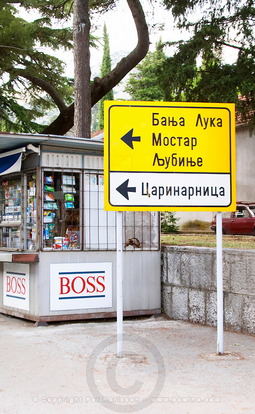 Road sign in front of a news stand kiosk pointing to Mostar Federation Bosne i Hercegovine. Bosnia Herzegovina, Europe.