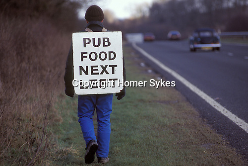 Village Pub food. Sandwich board  man walking along the A 303 road in Wiltshire England