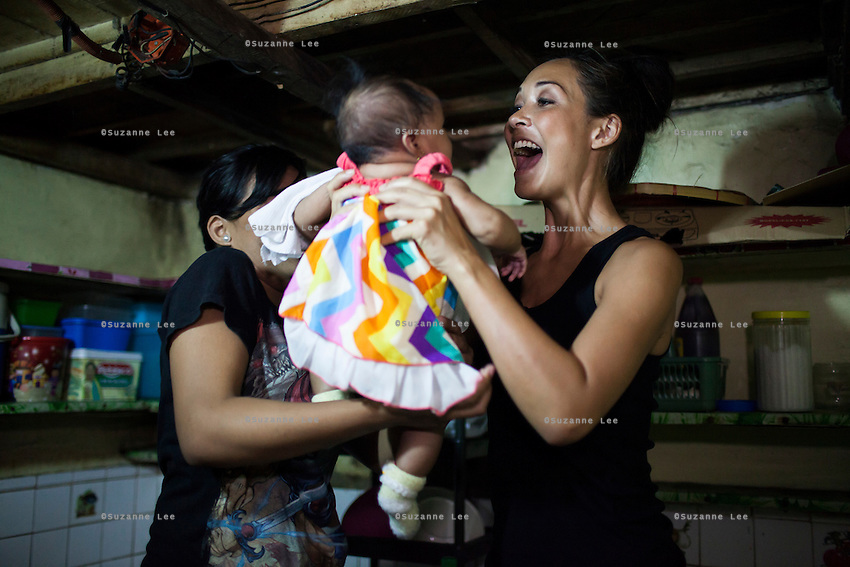 Myleene Klass, a celebrity from the UK, meets single mother Josephine Savares, 18, as she holds her 1st child Jihan, aged 4 months, in her family house, in Paranaque, Metro Manila, The Philippines on 19 January 2013. Josephine had decided to feed her baby formula during her pregnancy and had no idea that her father had to pay such a high price for it. Her family goes without food some days, and her siblings have had to stop school in order to afford the formula. Photo by Suzanne Lee for Save the Children UK