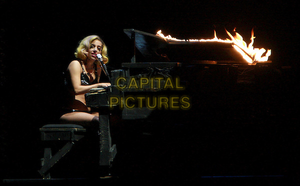 LADY GAGA (Stefani Joanne Angelina Germanotta) .performs live during Monster Ball 2010 North American Tour at the Pepsi Center in Denver, Colorado, USA,.July 28th 2010..music concert gig on stage half length black conical cone bra top pvc silver studded studs knickers  microphone singing sitting at piano  playing  flames on fire alight burning                                                              .CAP/RKE/RT.©Rod Tanaka / RockinExposures/Capital Pictures.