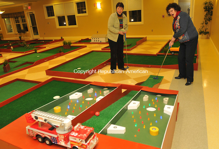 WOODBURY, CT-11 FEBRUARY 2009-021110IP06-Sharon Sherman (left) and Pat Barre, both of Woodbury, compete during the Woodbury 2nd Annual Indoor Miniature Golf Open at the Woodbury Senior/Community Center on Thursday. The course is open for play until February 16th and net proceeds will go to the Woodbury Historic Town Hall Restoartion Fund.  People can play Friday, Saturday, Sunday and Monday from 9am to 9pm and Tuesday February 16 from 9am to 8pm. Woodbury resident Charles Bartlett built the course in his basement along with a handful of volunteers.<br /> Irena Pastorello Republican-American