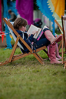 Tuesday 27 May 2014, Hay on Wye, UK<br /> Pictured: People sit and read on the Green at the Hay Festival<br /> Re: The Hay Festival, Hay on Wye, Powys, Wales UK.