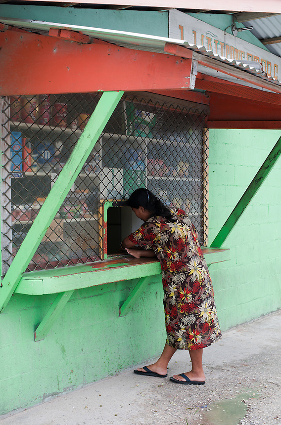 A young woman leans on a shop window in Majuro, Marshall Islands.