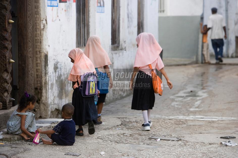 Afrique/Afrique de l'Est/Tanzanie/Zanzibar/Ile Unguja/Stone Town: dans les rues de la vieille ville. enfants et écolières devant une vieille porte de la ville