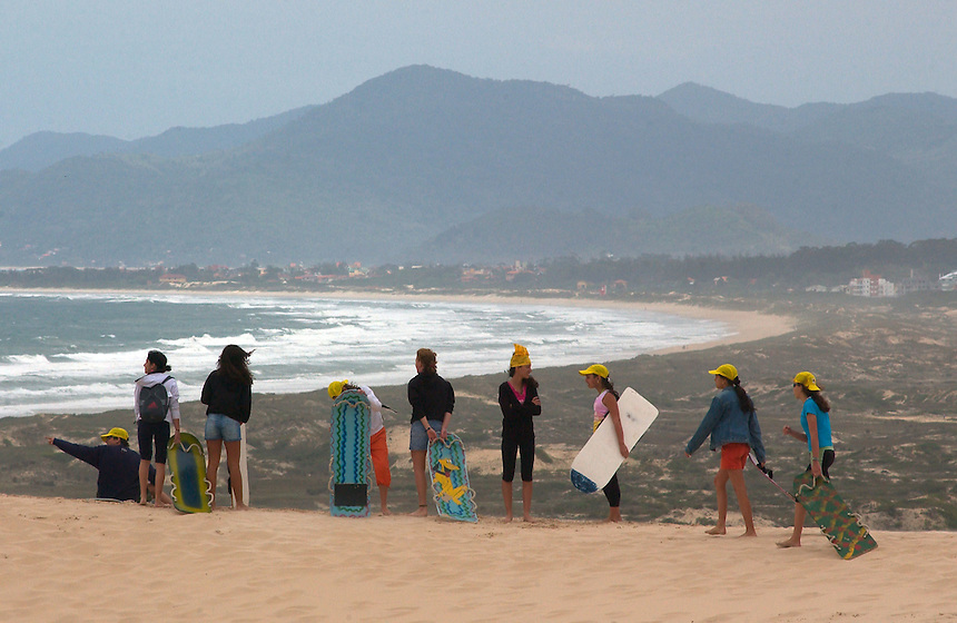 Visiting high school students line the top of a dune over Praia Joaquina to sand surf on Santa Catarina Island in southern Brazil. The island has long been a destination for beach-loving Brazilians. (Kevin Moloney for the New York Times)
