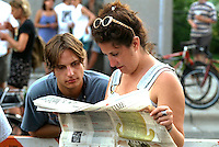 Couple age 28 reading newspaper at Bastille Day celebration.  Minneapolis Minnesota USA