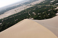 Aerial view of sand encroaching upon local farmland. Desertification is the process by which fertile land becomes desert, typically as a result of drought, deforestation, or inappropriate agriculture. 41 % of China's landmass in classified as arid or desert. Innapropriate farming methods and overcultivation have contributed to the spreading of deserts in China in recent years. The desert has even encroached upon the capital, Beijing, which is bombarded by sandstorms each spring. Dunhuang, Gansu Province. China