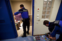 Switzerland. Geneva. A police officer is strip searching a prisoner in a cell at the Paquis police station. The young man was arrested because he kicked a police car after a breakup with his girlfriend. The inmate is a swiss adolescent. A strip search is a practice of searching a person for weapons or other contraband suspected of being hidden on their body or inside their clothing by requiring the person to remove some or all of his clothing. The strip search is a mandatory procedure which requires legal authority. It is done by a police officer once a person is arrested and locked in a cell. A police station or station house is a building which serves for police officers. The building contains temporary holding cells and interview/interrogation rooms. Both policemen are wearing a ballistic vest, bulletproof vest or bullet-resistant vest which is an item of personal armor that helps absorb the impact from knives, firearm-fired projectiles and shrapnel from explosions, and is worn on the torso. Soft vests are made from many layers of woven or laminated fibers and can be capable of protecting the wearer from small-caliber handgun and shotgun projectiles. 5.05.12 © 2012 Didier Ruef