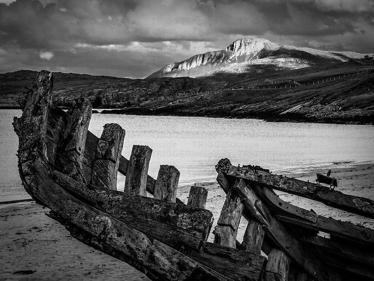 Close upof old wooden boat derelict on the shore beneath snowy mountains