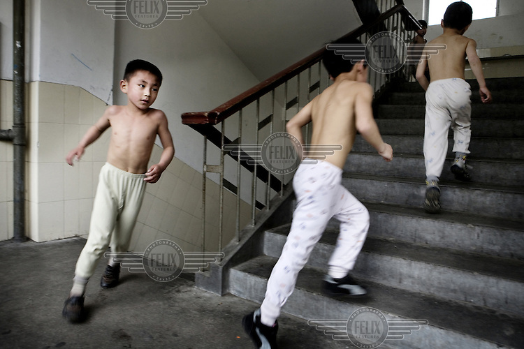 School children at the Li Xiaoshuang Gymnastic School in Xiantao running up and down the stairs as part of their training. It is an elite school for children with a special talent in gymnastics or acrobatics. The school day consists of a mix of sports and traditional academic studies.