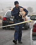 Douglas County Sheriff's Deputy Jesse McKone carries a dog out of a Fish Springs home where officials arrested 81-year-old Melvin Norlund on Thursday afternoon, Nov. 21, 2013, after he allegedly shot and killed his caretaker with a shotgun.<br /> Photo by Cathleen Allison