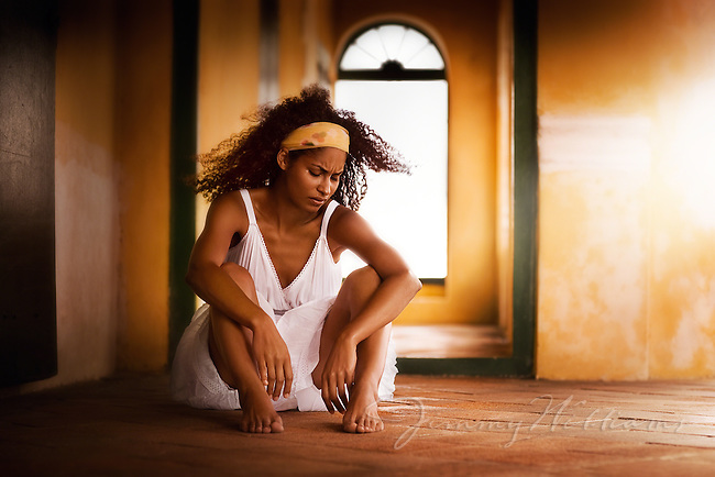 An african-american woman sits barefoot inside of an old fort crying.