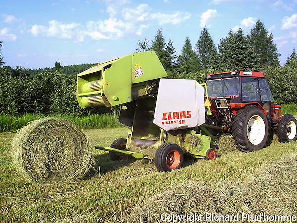 Farm tractor is stopped to open up back door of a Class 46  baler to let round bale of hay out, Once the chamber of the baler is full, string is wound around bale of hay several times  to help hold it together once it is let out of baler.  This hay will be used to feed cattle during the winter.