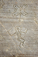Petroglyph, rock carving, of a warrior  carrying with a sword and a round shield and wearing a halo helmet dancing around the so called Camunian Rose. Carved by the ancient Camuni people in the iron age between 1000-1600 BC. Rock no 24,  Foppi di Nadro, Riserva Naturale Incisioni Rupestri di Ceto, Cimbergo e Paspardo, Capo di Ponti, Valcamonica (Val Camonica), Lombardy plain, Italy