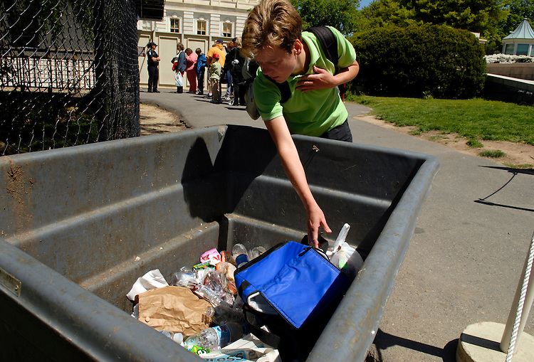 A tourist tries to recover a belonging after disposing of it before entering the Capitol.  Food items and liquids such as perfume are not allowed on tours.