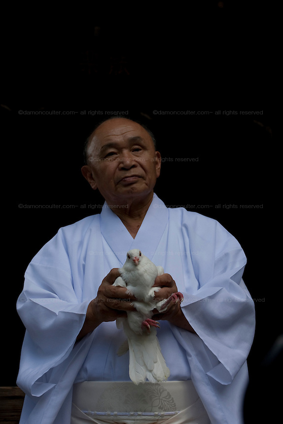 A priest holds a dove before releasing it as a prayer for peace at Yasukuni Shrine. On August 15th every year people gather at Yasukuni Shrine to commemorate the end of the Pacific War. Notionally a call for remembrance and continued peace it is also a Mecca for right wing nationalist including  the paramilitary Uyoku Dantai. Tokyo, Japan, August 15th 2009