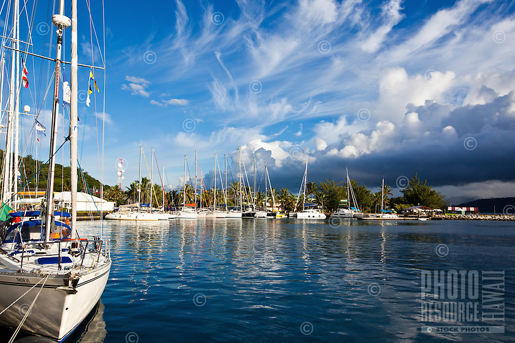 Uturoa Harbor with yachts tied to dock, with dramatic clouds above