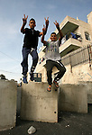 Palestinian boys jump over cement blocks at a newly erected checkpoint in Jerusalem's neighborhood of Jabal al-Mokaber on October 19, 2015. Israeli police began erecting a wall in east Jerusalem to protect a Jewish neighbourhood subject to firebomb and stone attacks launched from an adjacent Palestinian village. Photo by Mahfouz Abu Turk
