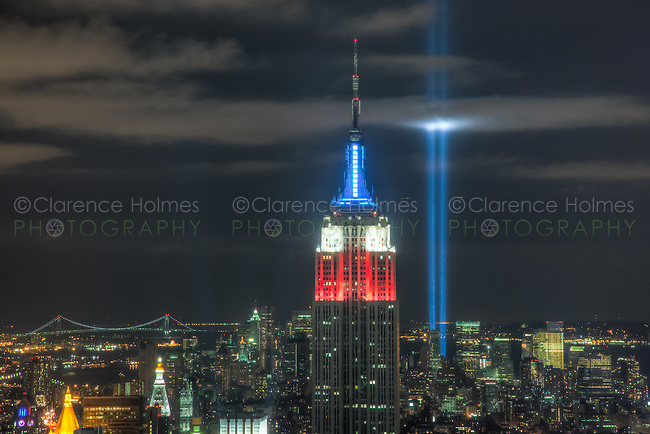 The twin beams of light of the Tribute in Light, a memorial to the events of September 11, 2001, shine into the evening sky behind the Empire State Building.
