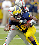 Ohio State defensive back C.J. Barnett (4) wraps up Michigan quarterback Denard Robinson (16), in the second quarter of an NCAA college football game, Saturday, Nov. 26, 2011, in Ann Arbor, Mich. (AP Photo/Tony Ding)