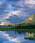 Banff National Park, Alberta, Canada:  Mount Rundle reflecting on Vermillion Lakes with sun breaks lighting the distant wetland trees