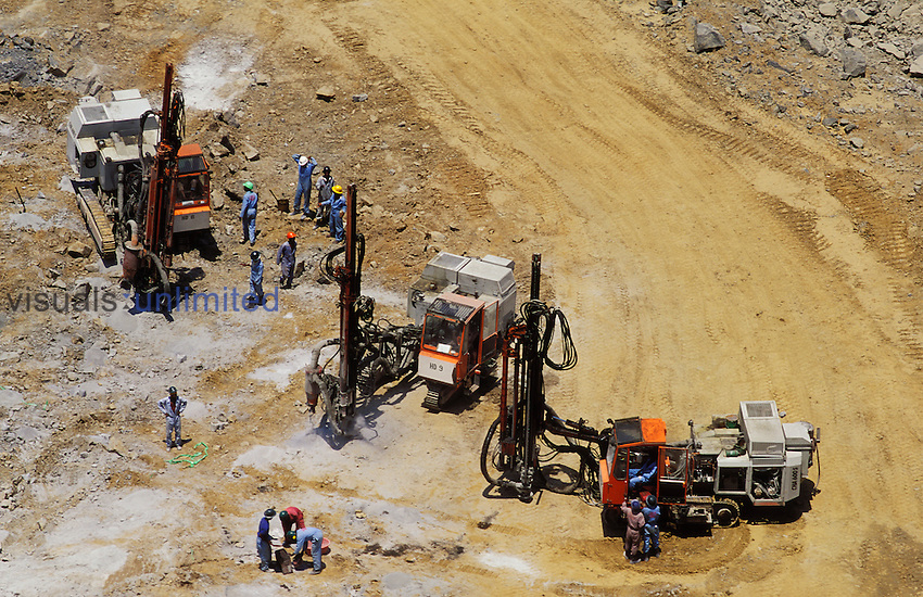 Mobile drilling rigs working on bore holes for blasting in an open cast gold mine, Zimbabwe, Southern Africa.