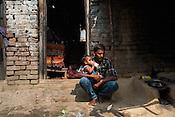 Seema Devi's husband, Vinay Paswan (22) takes care of their 9 month old daughter, Vaishnavi Kumari in their kitchen of their hut in Shivpur Hariyya village in Raxaul district of Bihar.