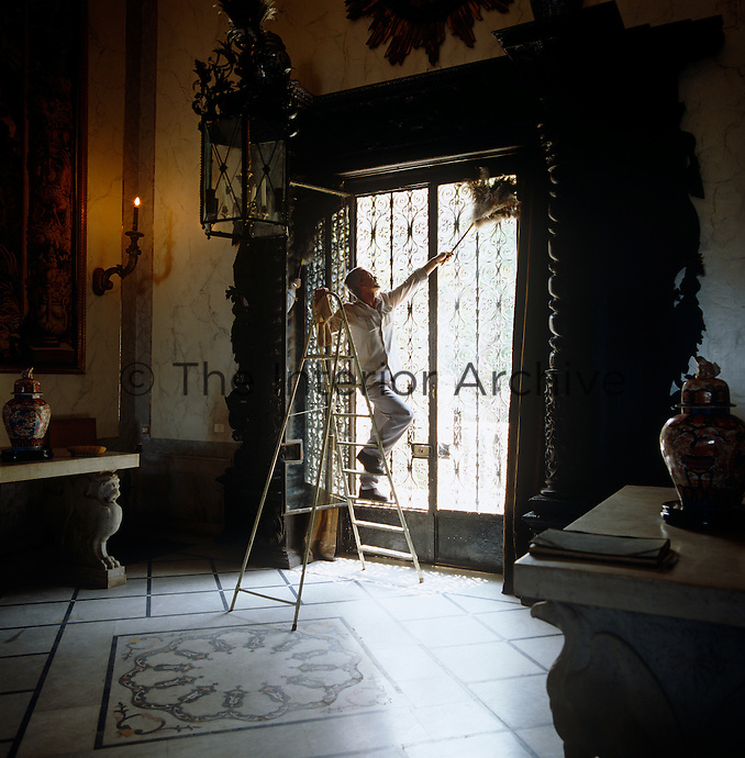 A man on a stepladder dusts the glass door in the dark entrance hall which features a patterned stone floor