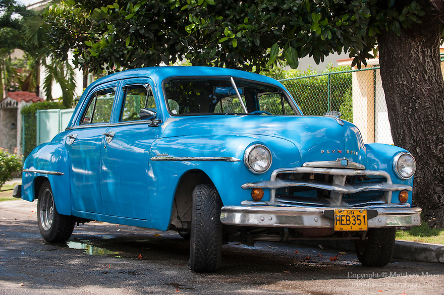 Havana, Cuba; a blue classic 1950 Plymouth parked under a tree along the road