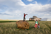 Children of University of Pittsburgh researchers, Alex Galick, 9, tosses a stick over the heads of Emma Capo Stewart, 13, brother Owen Capo Stewart, 3, in the yard of rancher Allen Cook. Cook recently donated a large piece of his Wyoming ranch to the University of Pittsburgh for research. The ranch property features cretaceous rock formations preservibg dinosaur fossils, high-plains grassland ecology and interesting tectonic geology for study by the students and faculty of Pittsburg, the University of Wyoming and the Carnegie Museum. (photo/Kevin Moloney)