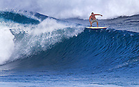Surfer riding the crest of an 18-plus foot wave at Banzai Pipeline on North Shore of Oahu.