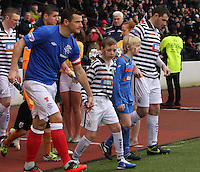 Club captains Lee McCulloch (left) and Anthony Quinn lead their teams out with mascots in the Queen's Park v Rangers Irn-Bru Scottish League Division Three match played at Hampden Park, Glasgow on 29.12.12.