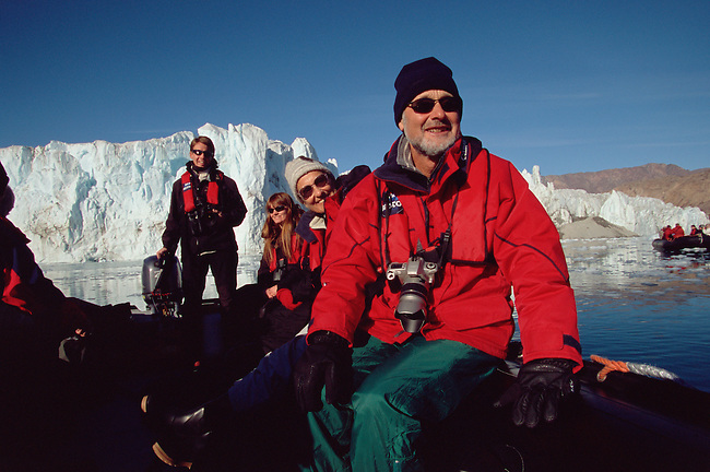 Manfred Tschipper sits at the front of the Zodiac as it cruises the Eielson Glacier in Rype Fiord. Scoresbysund. East Greenland.