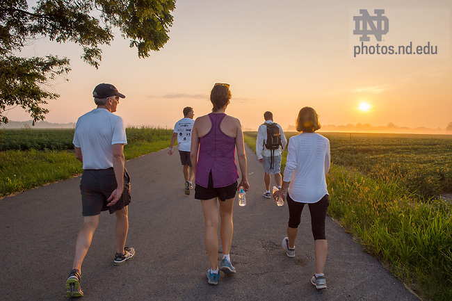 August 15, 2017; On Day 2 of the ND Trail, University of Notre Dame President Rev. John I. Jenkins, C.S.C., and Ann Firth, Chief of Staff, (center) make the 39 mile trek, 18 walking and 21 biking with fellow pilgrims on the ND Trail from Oaktown to Pimento, Indiana. As part of the University's 175th anniversary celebration, the Notre Dame Trail will commemorate Father Sorin and the Holy Cross Brothers' journey. A small group of pilgrims will make the entire 300+ mile journey from Vincennes to Notre Dame over  two weeks. (Photo by Barbara Johnston/University of Notre Dame)