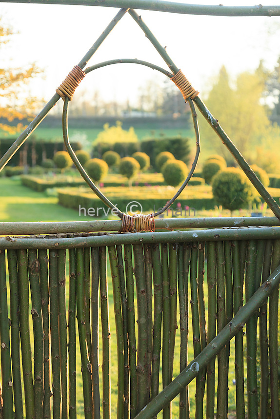 Jardin de la Ferme du Mont des R&eacute;collets:<br /> portillon fait en branches de saule vers le jardin des carr&eacute;s de buis. // France, garden of Ferme du Mont des R&eacute;collets, gate made ​​of green willow branches
