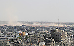 Smoke from an Israeli strike rises over the Gaza Strip, Friday, July 25, 2014. Israeli warplanes struck houses throughout the Gaza Strip as international efforts continue to broker a cease fire in the 18 day-old war. Photo by Yasser Qudih
