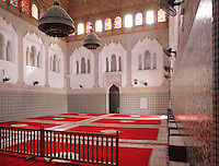 Interior of the Mausoleum of Moulay Idriss I, open only to non-muslims, with carpeted floor, tiled walls, horseshoe arch windows and stained glass, Moulay Idriss, Meknes-Tafilalet, Northern Morocco. The mausoleum was rebuilt by Moulay Ismail, 1672-1727, in the 17th century and is the site of an important moussem or pilgrimage festival each summer. The town was founded by Moulay Idriss I, who arrived in 789 AD and ruled until 791, bringing Islam to Morocco and founding the Idrisid Dynasty. His body was moved to a tomb in the mausoleum. Picture by Manuel Cohen