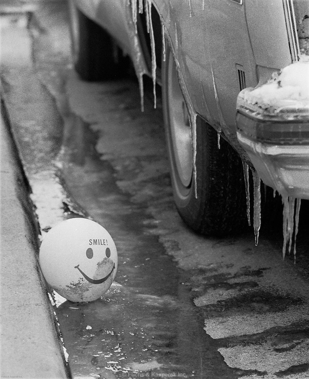 A baloon with a smiley face sits in the gutter after a winter storm. Jackson, Miss., 1979