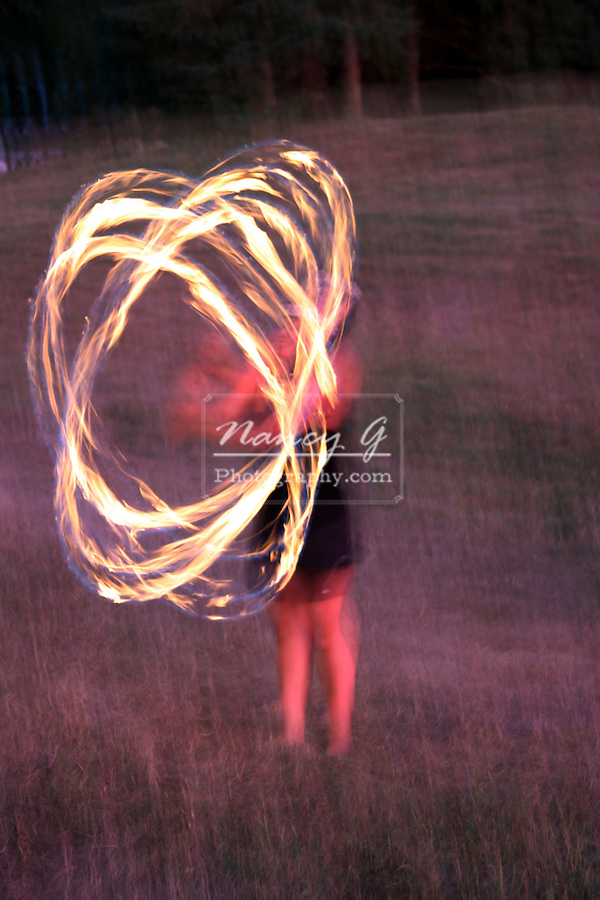 The glow of a female Hawaiian Fire Dancer performing at night