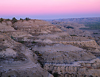 NDTR_116 - USA, North Dakota, Theodore Roosevelt National Park, Sunset glow in sky over sedimentary hills and valley of the Little Missouri River, view east from River Bend Overlook, North Unit.