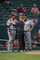 Salt Lake Bees catcher Jose Briceno (10) is examined by the team trainer and manager Keith Johnson (21) after taking a ball of his hand during a Pacific Coast League game against the Fresno Grizzlies at Chukchansi Park on May 14, 2018 in Fresno, California. Fresno defeated Salt Lake 4-3. (Zachary Lucy/Four Seam Images)