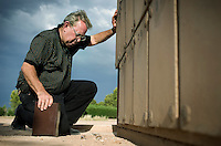 Ron Adair (cq) of Adair Funeral Home pauses for a moment before placing the ashes of an unidentified body into a niche inside a columbarium built at the Pima County Fiduciary Cemetery at Evergreen Cemetery in Tucson, Arizona, Tuesday, August 12, 2009. The person was found near the Robles Junction in Arizona in November 2006. ..PHOTOS/ MATT NAGER