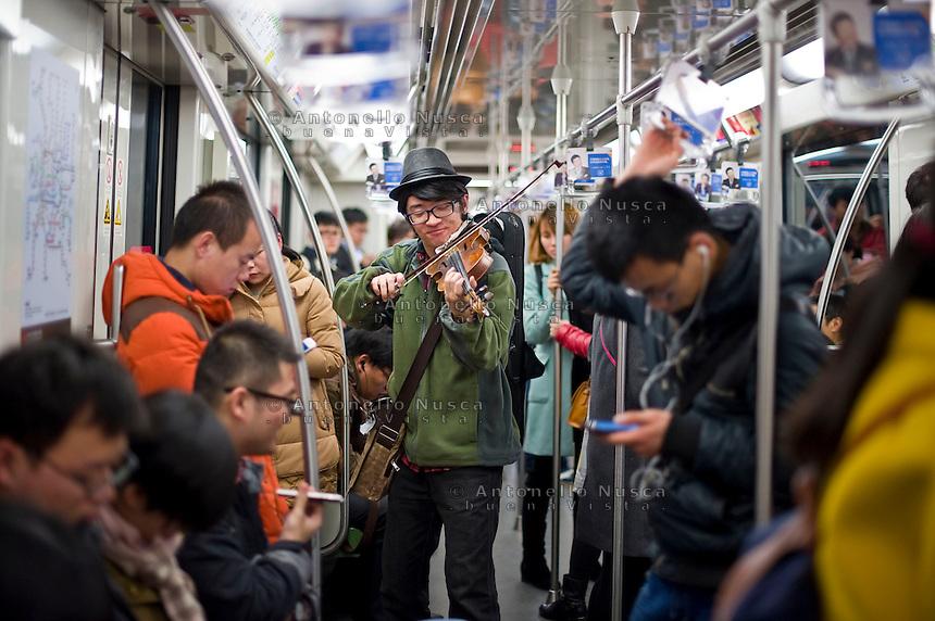 Un musicista nella metropolitana di Shanghai.<br /> A musician plays in the subway car