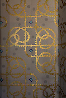 Hand printed wallpaper using gold leaf by Atelier d'Offard, using interlacing patterns reminiscent of the Neo-Romanesque period of the 19th century, in the Bell tower room themed 'Le Merveilleux' or The Supernatural, first floor, in Le Tresor de la Cathedral d'Angouleme, in Angouleme Cathedral, or the Cathedrale Saint-Pierre d'Angouleme, Angouleme, Charente, France. The 12th century Romanesque cathedral was largely reworked by Paul Abadie in 1852-75. In 2008, Jean-Michel Othoniel was commissioned by DRAC Aquitaine - Limousin - Poitou-Charentes to display the Treasure of the Cathedral in some of its rooms, which opened to the public on 30th September 2016. Picture by Manuel Cohen. L'autorisation de reproduire cette oeuvre doit etre demandee aupres de l'ADAGP/Permission to reproduce this work of art must be obtained from DACS.