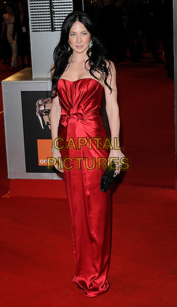 LYNN COLLINS.Arrivals at the Orange British Academy Film Awards 2010 at the Royal Opera House, Covent Garden, London, England, UK, .21st February 2010.BAFTA BAFTAs full length strapless red dress bow ruched long maxi black clutch bag.CAP/CAN.©Can Nguyen/Capital Pictures