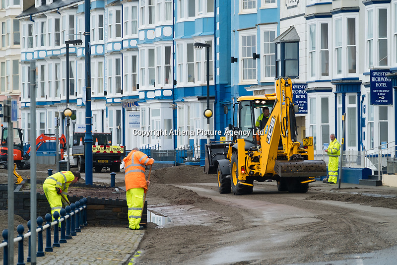 """Pictured: Council workers and diggers clear debris off the promenade of the seaside town of Aberystwyth, Wales, UK. Monday 23 October 2017<br /> Re: A clean operation is under way at coastal parts of the UK were affected by Storm Brian.<br /> Roads in Aberystwyth's seafront and at nearby Aberaeron, Wales were shut on Saturday morning as a yellow """"be aware"""" Met Office warning is in place."""