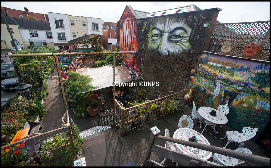BNPS.co.uk (01202 558833)<br /> Pic: TomWren/BNPS<br /> <br /> Chaplins & The Cellar Bar has been awarded Britain's best beer garden.<br /> <br /> A beer garden likened to 'the set of a David Lynch film' has been named the best in the country. <br /> <br /> Chaplin's Cellar Bar's backyard lay empty and practically unused until it was bought by Harry Seccombe, formerly the owner of a local builders' merchants, a decade ago.<br /> <br /> But now punters can sip their drinks surrounded in a three-level haven of exotic plants, druid style murals and even a suit of armour following a radical transformation. <br /> <br /> And in recognition of this innovation the pub, located in a busy suburb of Bournemouth in Dorset, has been awarded the title of having 'Britain's Best Beer Garden 2016'.